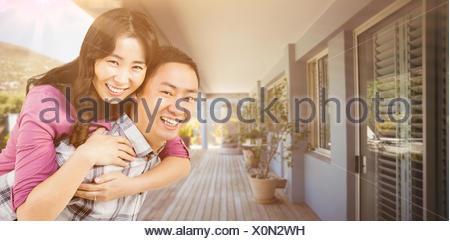 Image composite de man giving woman piggyback un Banque D'Images