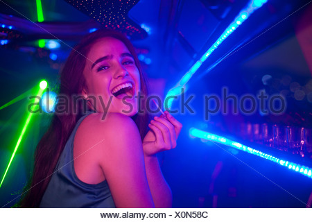 Young woman laughing at bar in nightclub Banque D'Images