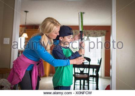 L'enseignement de mère fils de tenir une batte de baseball Banque D'Images