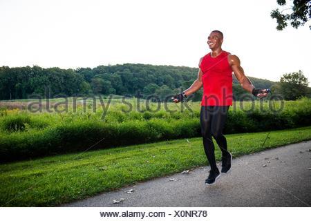 La formation jeune homme avec la corde à sauter sur le chemin Banque D'Images