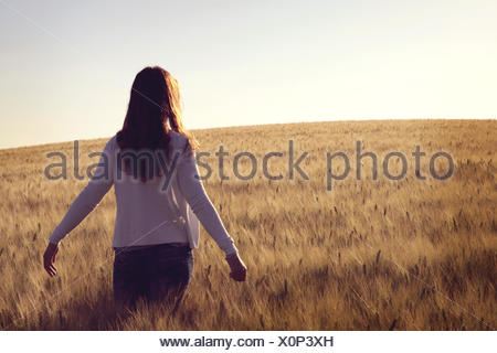 Woman standing in wheat field Banque D'Images