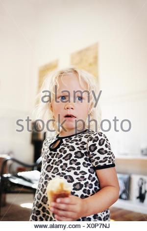 Portrait de jeune fille blonde (4-5) eating sweet bun Banque D'Images