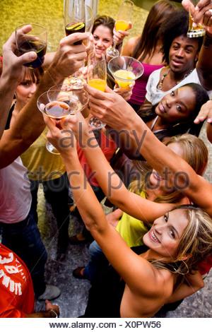 Groupe d'amis heureux dans un bar ou une discothèque à élever leurs verres Banque D'Images