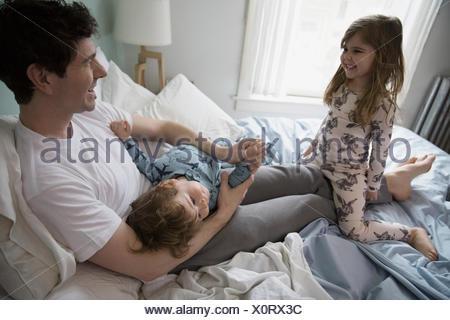 Le père et les enfants en pyjama playing in bed Banque D'Images