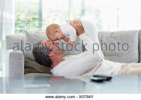 Heureux père jouant avec son mignon bébé fille à la maison Banque D'Images