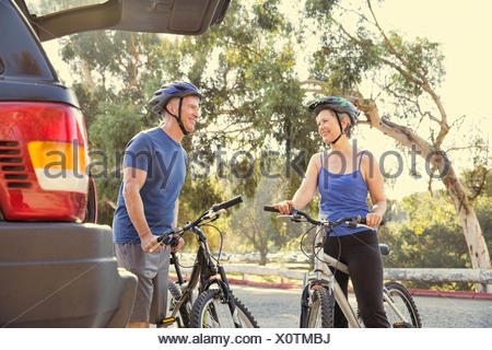 Cycliste mature couple chatting in park Banque D'Images