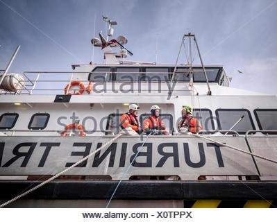 Les ingénieurs de parc éolien offshore en port sur navire Banque D'Images