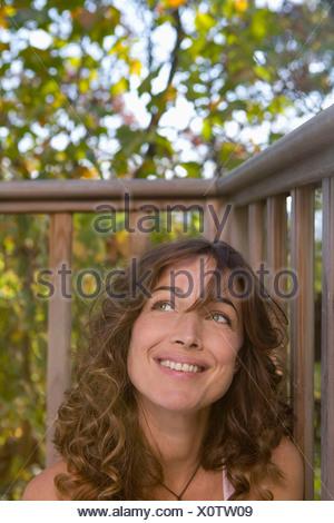 Femme assise sur le balcon en souriant. Banque D'Images