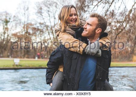 Young woman getting piggyback de copain sur Riverside Park Banque D'Images