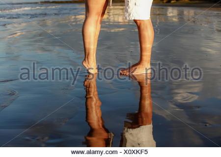 La section basse de jeune couple standing on beach Banque D'Images