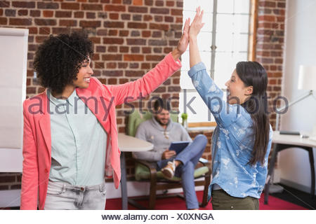 Collègues femmes high fiving in office Banque D'Images