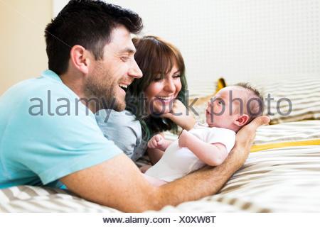 Heureux parents jouer avec bébé garçon (6-11 mois) on bed Banque D'Images