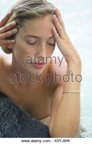 Woman relaxing in pool Banque D'Images