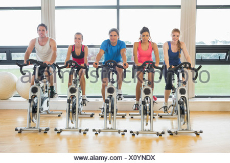 Cinq déterminé people working out at spinning class Banque D'Images