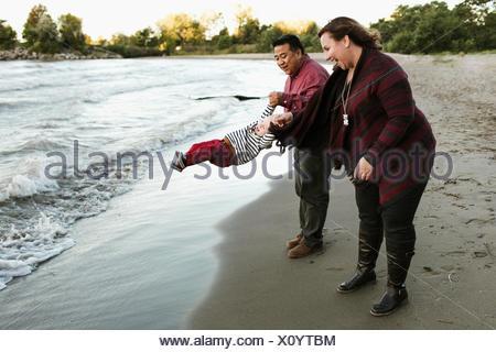 Mère et père sur beach swinging baby boy, Toronto, Ontario, Canada Banque D'Images