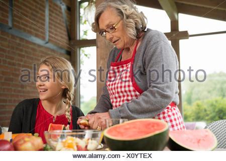 Grand-mère et fille à l'apprentissage de la table de cuisine de fruits frais en tranches Banque D'Images