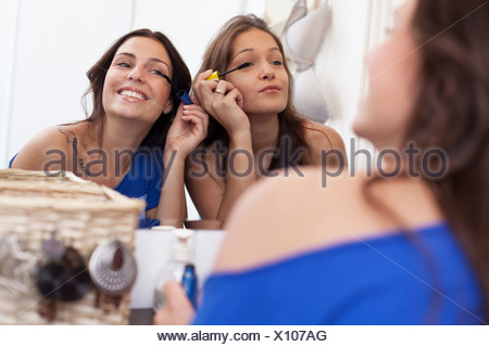 Smiling women appliquant le maquillage dans le rétroviseur Banque D'Images