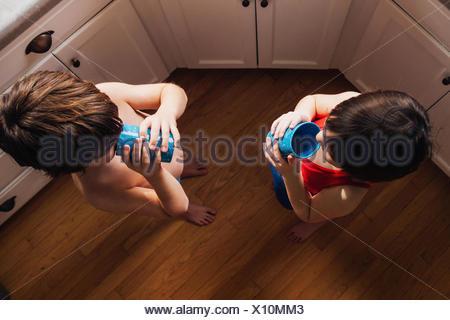 Garçon et fille debout dans l'eau potable de cuisine Banque D'Images