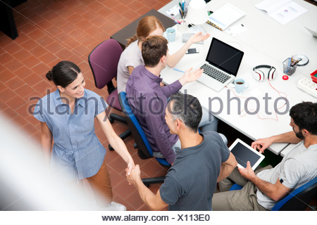 Colleagues shaking hands, high angle Banque D'Images