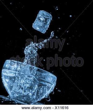 Ce cube flying water splash sur ciel noir Banque D'Images