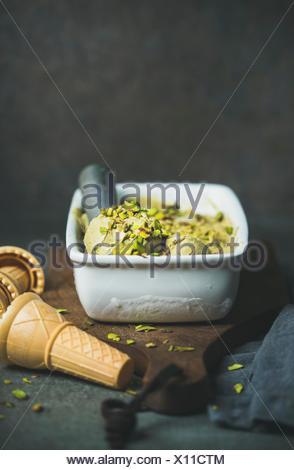 Des Glace Pistache en moule en céramique avec une pelle métallique, écrasa les pistaches et les cônes alvéolés sur fond de béton, copy space Banque D'Images