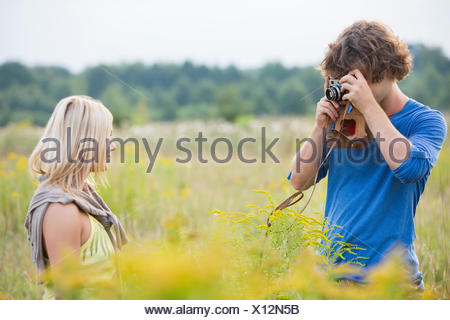 Young man photographing woman in field Banque D'Images