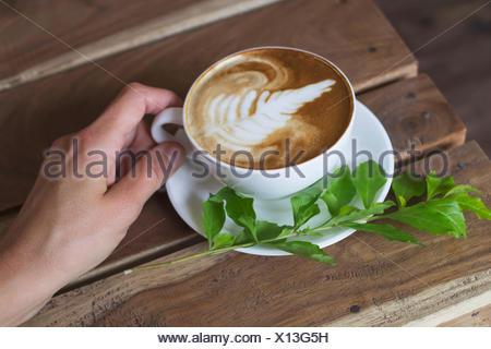 Femme tenant une tasse de cappuccino