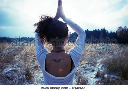 Mid adult woman practicing yoga de l'arbre debout Banque D'Images