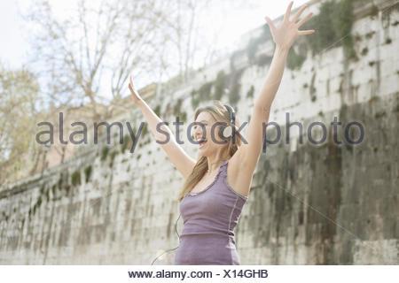 Happy young woman, portant des écouteurs et raising arms Banque D'Images
