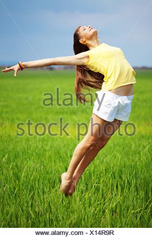 Belle jeune fille faisant des sauts de gymnastique en plein air Banque D'Images