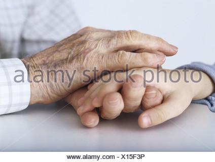 Les mains du grand-père de l'enfant l'étreinte part Banque D'Images