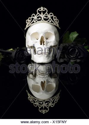 Crâne humain portant tiara et roses noires Banque D'Images