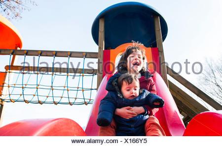 Garçon et frère bébé glissant sur aire de glisse Banque D'Images