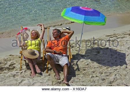 Couple de personnes âgées se trouvant dans la région de chaises en toile sur plage de sable fin, Baléares, Ibiza Banque D'Images