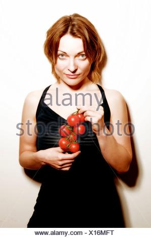 Une jeune femme tenant un bouquet de tomates de vigne Banque D'Images