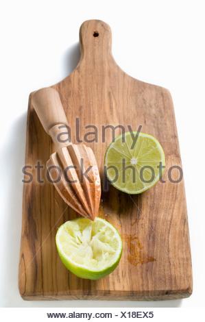 Deux moitiés de citron vert pressé sur une planche à découper FoodCollection Banque D'Images
