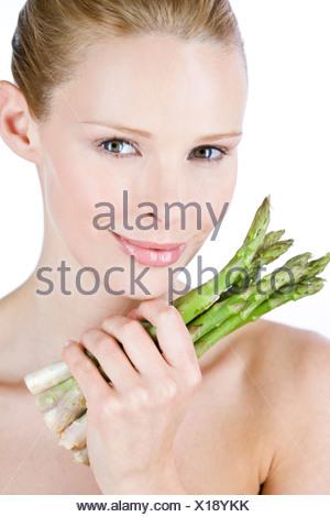 Une jeune blonde woman holding a bunch of asparagus, close-up Banque D'Images
