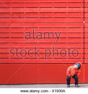 Garçon en rouge qui s'est bousillé devant un mur rouge Banque D'Images