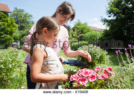Smiling mother and daughter in jardin planter des fleurs Banque D'Images