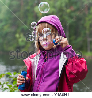 Girl blowing bubbles outdoors Banque D'Images