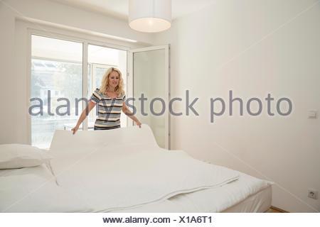 Femme mature dans la chambre lit en couverture de portefeuille Banque D'Images