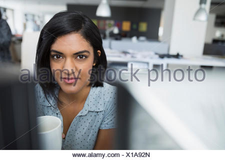 Portrait of businesswoman drinking coffee at office desk Banque D'Images