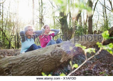 Les femmes dans les mains derrière la tête de faire s'asseoir contre l'arbre tombé Banque D'Images