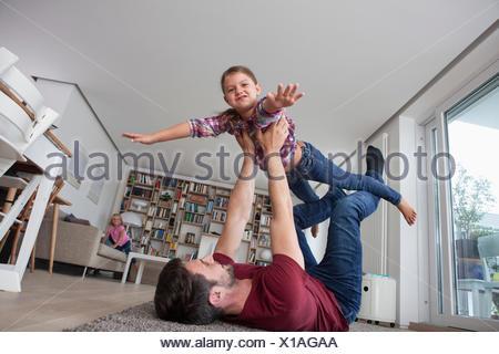 Homme étendu sur le plancher au salon de jouer avec sa petite fille Banque D'Images