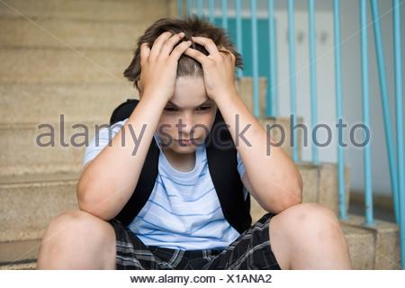 Un pré-adolescents inquiets boy sitting on stairs dans une école Banque D'Images