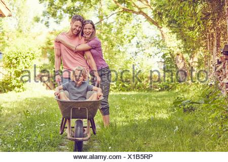 Portrait de jeune famille, père fils poussant en brouette Banque D'Images