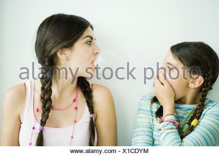 Deux jeunes amies, une bulle souffle alors que d'autres montres et couvrir la bouche Banque D'Images