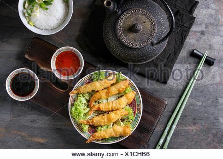 Poêlée de Crevettes tempura sur laitue salade avec des sauces. Servi dans la Chine traditionnelle avec des baguettes sur la plaque de bois servant de sélection. Théière, bol de riz. Ove Banque D'Images