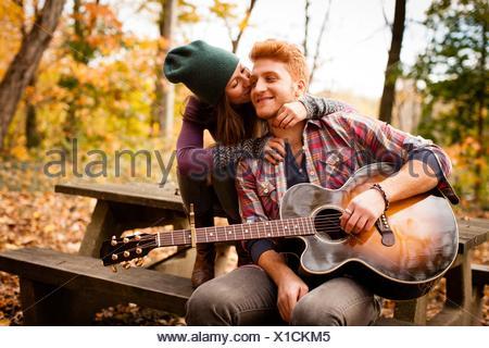 Jeune couple romantique qui joue de la guitare sur banc de pique-nique en forêt d'automne Banque D'Images