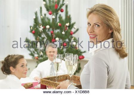 Femme portant une tablette avec verres de champagne Banque D'Images